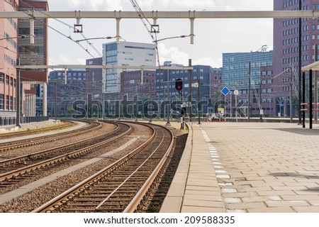 Platform with railway tracks in urban scenery of office buildings - stock photo