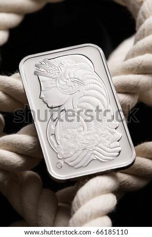 Platinum ingot on white rope - stock photo