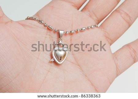 platinum pendant on hand and white background - stock photo