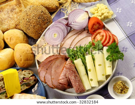 Platter full of fresh ingredients to make sandwiches along with selection of breads. - stock photo