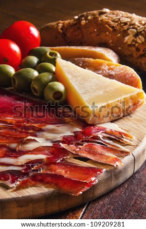 Platter of antipasti appetizers, with crusty bread (shallow dof) - stock photo