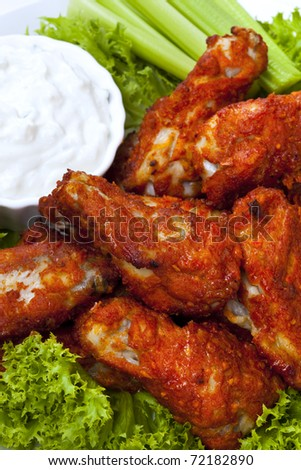 Platter of buffalo wings with a blue cheese dipping sauce and celery sticks.  Hot and spicy! - stock photo