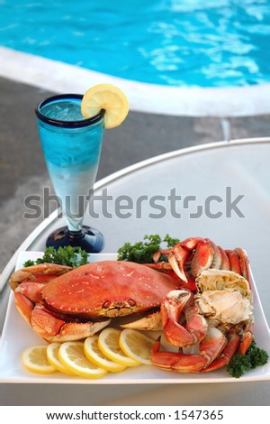 Platter of crab with lemon and parsley and a glass of sparkling water by the poolside