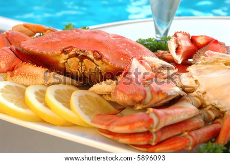 Platter of crab with lemon and parsley out by the pool - stock photo