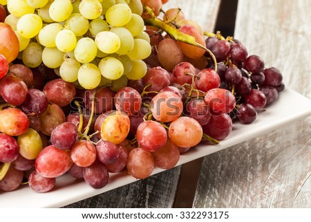 Platter of freshly harvested green and red grapes on a white square platter on an old barn wood table side view