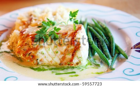 Platter of perfectly grilled sturgeon fish with sauce of white wine and side of green beans - stock photo