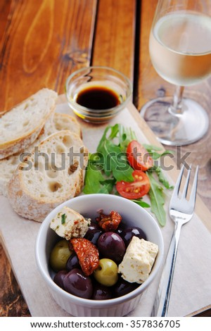 Platter with bread, olives, feta, side salad and a glass of wine  - stock photo