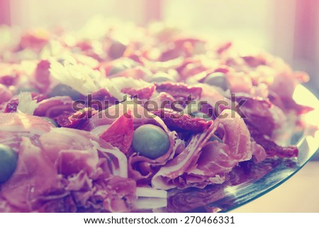 Platter with spanish cured ham on table, toned image - stock photo