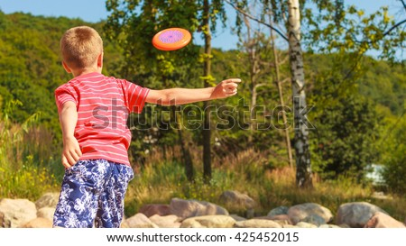 Play and fun concept. Little playful enjoyable boy kid throwing frisbee disc. Male child having fun playing outdoor on beach. - stock photo