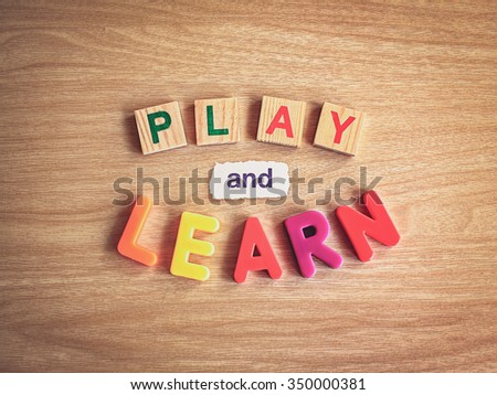 play and learn words on wooden background with retro style filter - stock photo
