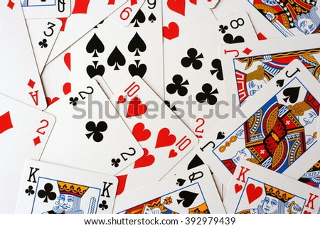 Play cards scattered on the table. Cards deck scattered. Play cards different colors. Play cards for bridge or poker (king, jack, queen...). Disarranged cards collection. - stock photo
