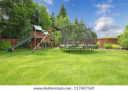 Play kinds ground area with trampling in fenced backyard during summer. - stock photo