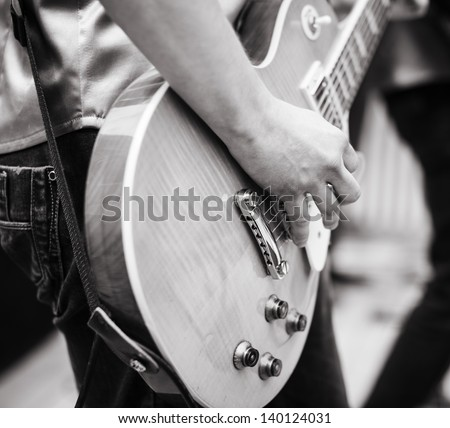 play on guitar, selective focus on part of hand and strings - stock photo