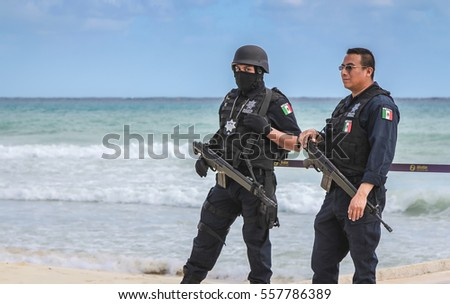 PLAYA DEL CARMEN, MEXICO - JANUARY 2012: Two military police officers patrolling  the beach in Playa Del Carmen during International Music Festival.