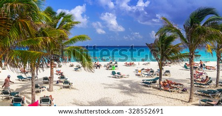 PLAYA DEL CARMEN, MEXICO - JULY 13, 2011: Unidentified tourists on the beach of Playacar at Caribbean Sea of Mexico. This resort area is popular destination with the most beautiful beaches. - stock photo