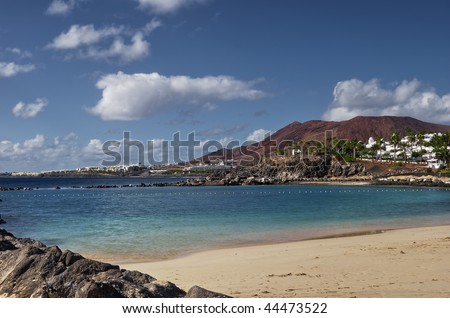 Playa Flamingo beach on the Spanish Canary Islands with Montana Roja volcano in the background. - stock photo
