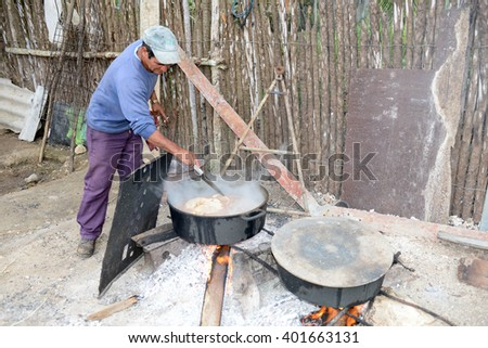 Playa Giron, Cuba - 20 january 2016: man boil meat and vegetables in two cauldrons on fire in the countryside of Giron on Cuba - stock photo