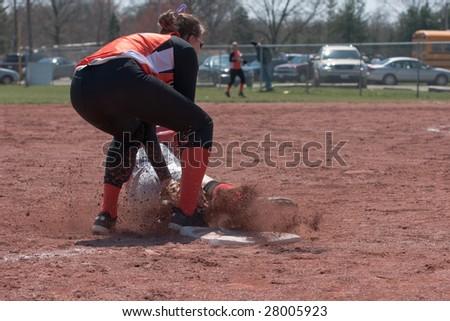 player applies tag to sliding runner at third base - stock photo