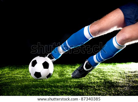 player hits the ball with his foot on the football field - stock photo