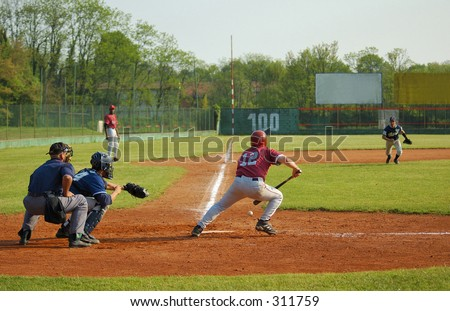 Player hitting ball and running to second base - stock photo