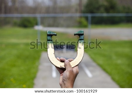 Player lines up to pitch a horseshoe in an outdoor court, hand and horseshoe in focus - stock photo