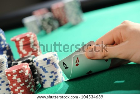 Player looking down at a pocket pair of aces in Texas Hold'em poker game