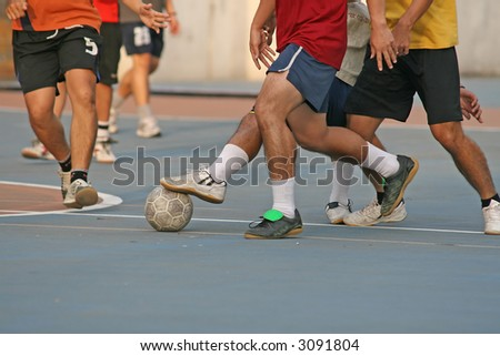 Player makes a tackle during a game of street football