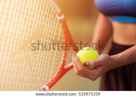 Player's hand with tennis ball preparing to serve in tennis cort.