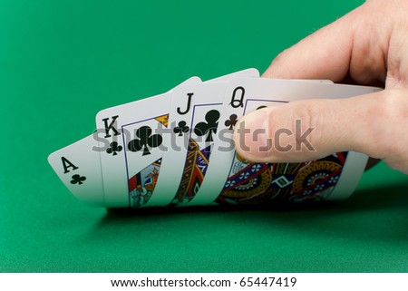 player's hand with the cards on the green game table