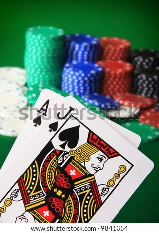 Player showing Black Jack against a big stack of chips blurred in the background. - stock photo
