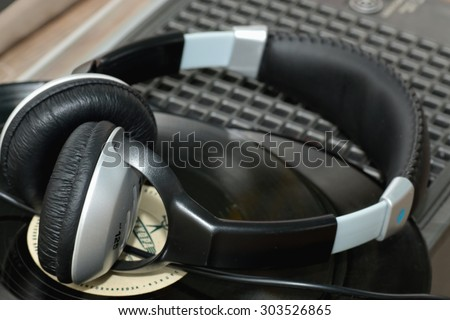 player with headphones on vinyl plates - stock photo