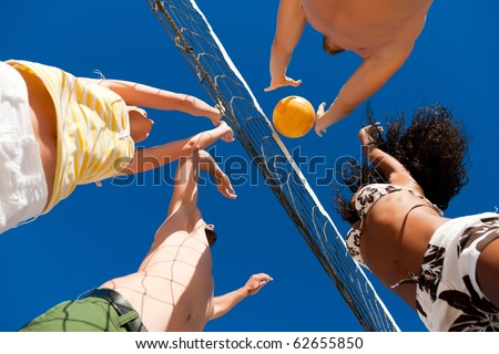 Players doing summer sports trying to block a dangerous attack in a beach volleyball game - stock photo