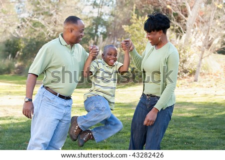 Playful African American Man, Woman and Child Having Fun in the Park. - stock photo