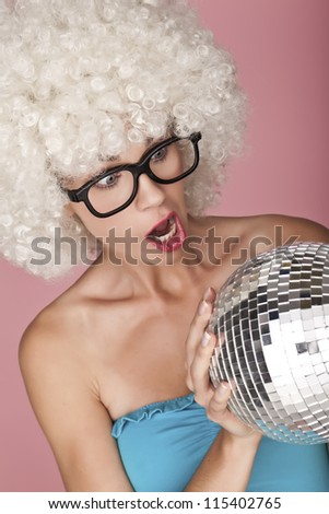 Playful and funny woman wearing a curly wig on a pink background. Funny face.