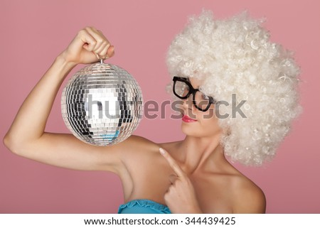 Playful and funny woman wearing a curly wig on a pink background. Having fun.