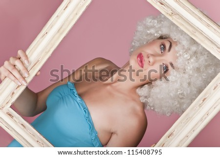 Playful and funny woman wearing a curly wig on a pink background. Sexy woman.