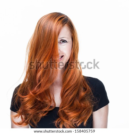 Playful and happy redhead woman with face partial covered by the long hairs on a white background
