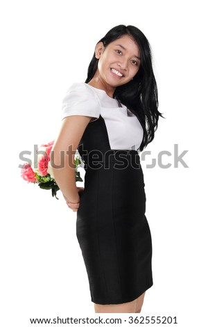 Playful Asian girl holds a bouquet of flowers on her back, isolated on white background - stock photo