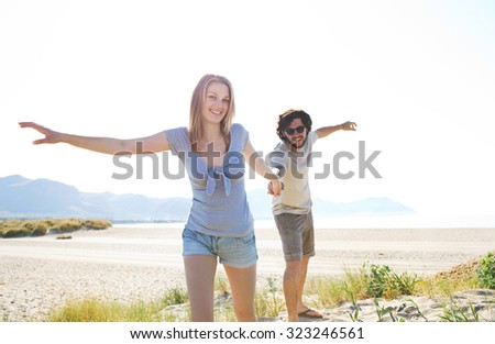 Playful beautiful tourist couple holding hands on a white sand beach with with pulling man playfully on holiday, coast outdoors. Travel and vacation lifestyle, nature living spacious exterior.