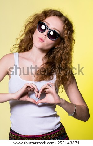Playful beautiful young woman with sunglasses making a heart gesture with her fingers to show her love and affection or that she likes something - stock photo