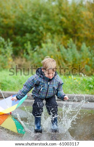 Playful boy jumping in puddle on rainy autumn day - stock photo