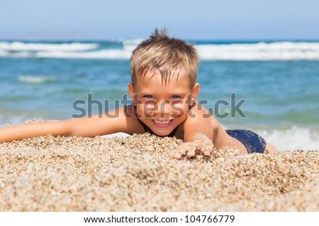 playful boy on the beach - stock photo