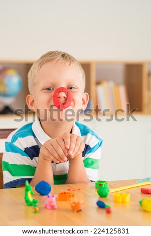 Playful boy posing with plasticine on his nose - stock photo