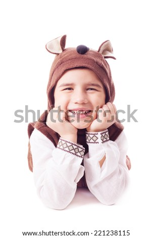 Playful boy wearing in a bear costume lies on a floor and holding head up with hands on face - stock photo