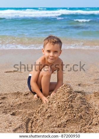 Playful boy with sand on the beach - stock photo