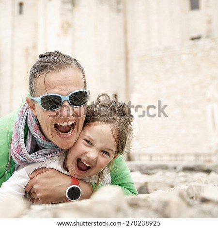 Playful Caucasian mother and daughter hugging, joking, making funny faces, smiling and having fun traveling and enjoying the summer. Natural, real situation.  - stock photo