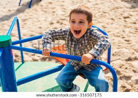 Playful child. Cheerful little boy expressing positivity while riding on roundabout - stock photo