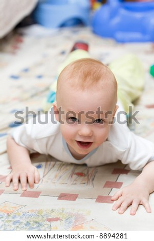 Playful child crawling on the carpet in living room - stock photo