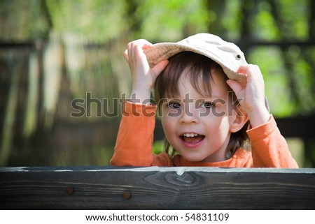playful child holding his hat - stock photo