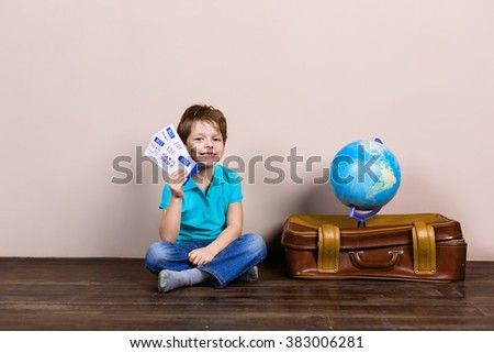 Playful childhood. Little boy going on trip. Boy sitting at suitcase near globe and holding tickets - stock photo